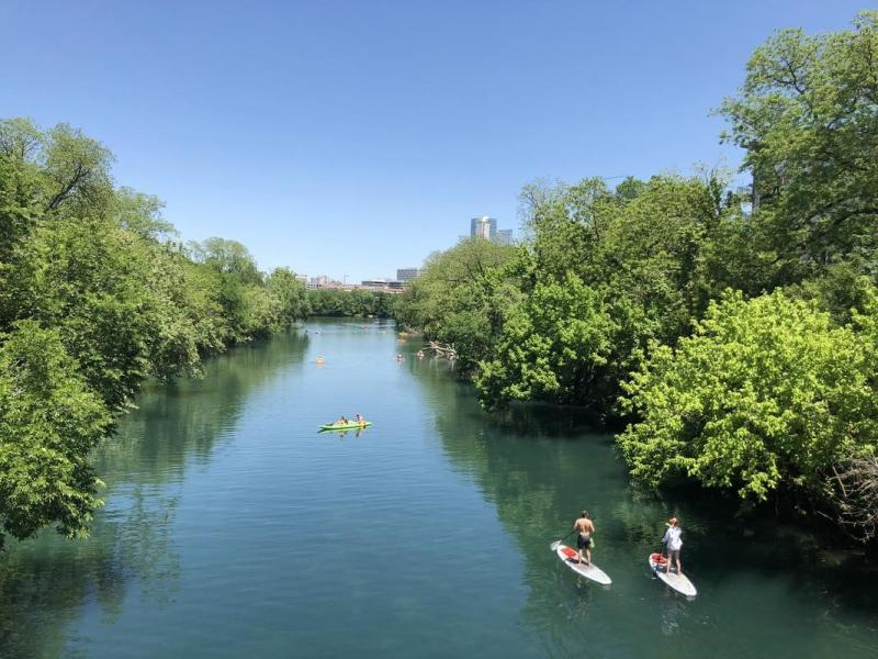 people kayaking and paddle boarding on lady bird lake near zilker park in austin texas