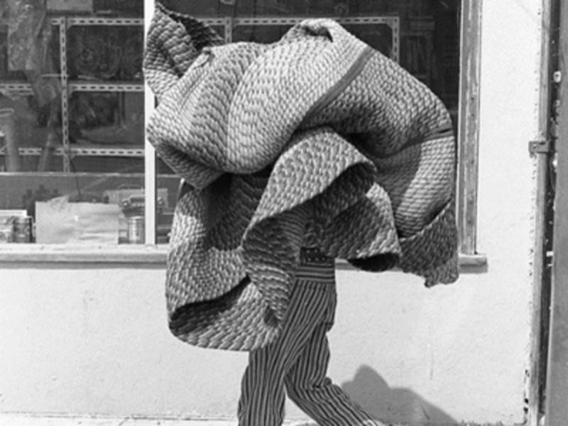 A black and white photo of a person walking down the street with an unrolled carpet held over their head.