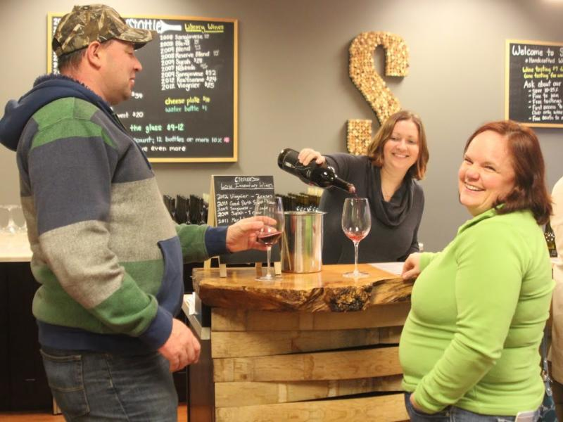 A woman pouring wine samples for man and woman during a tasting in Olympia, WA