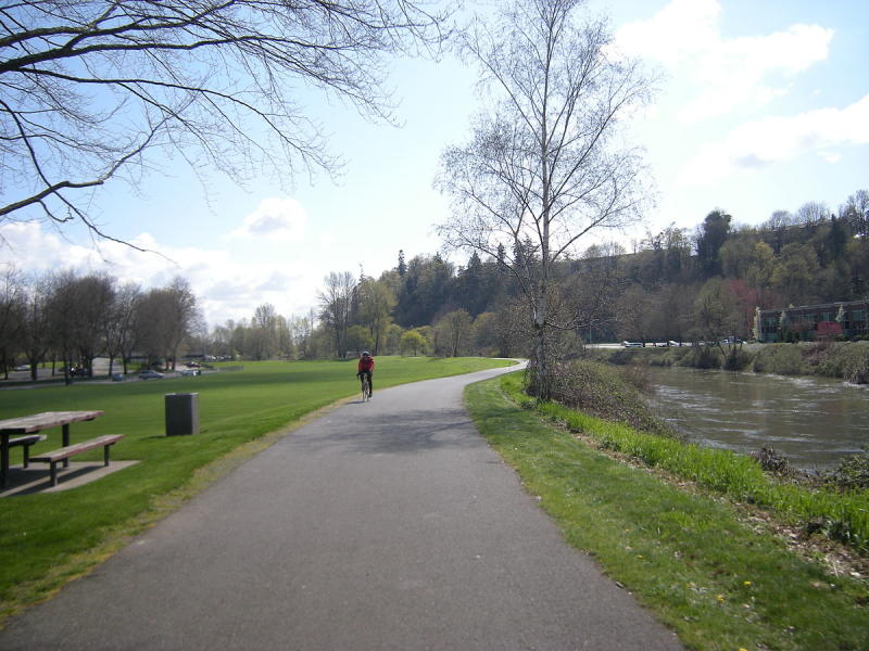Bicycle rider on Fort Dent Park river trail in Tukwila