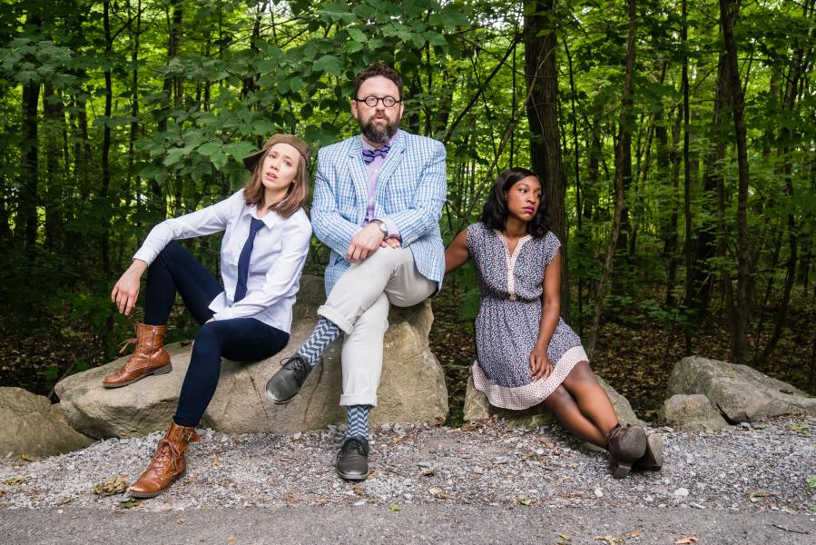 Actors from As You Like It sitting on rock in the woods