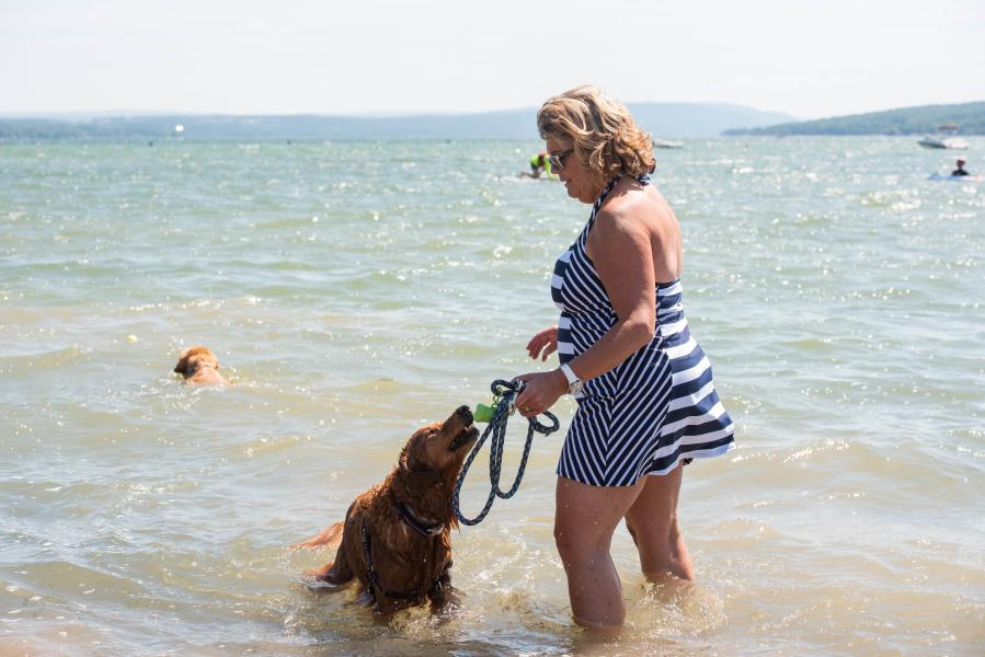 A woman plays with her dog in the water at Canandaigua Lake