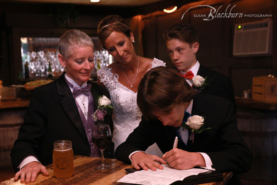 Couple during wedding with sons signing paper