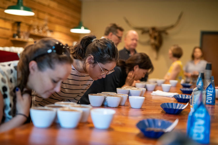 Photo of coffee lovers lean over coffee at Texas Coffee School during a cupping (tasting)