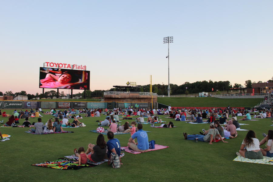 People enjoy a social-distance movie night in the Toyota Field outfield.