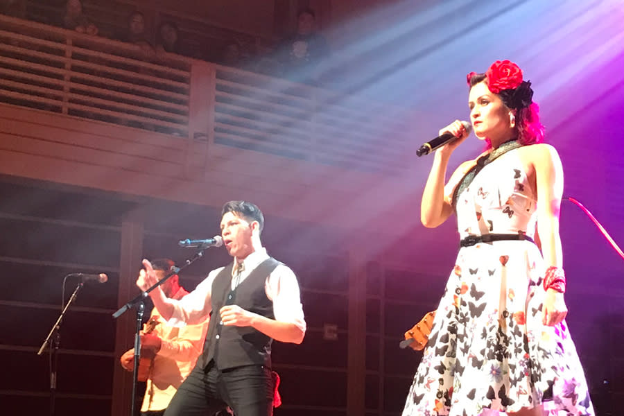 Chicano-rockabilly band Las Cafeteras - a woman in a white dress and a man in a dark vest sing on stage at Green Music Center in Sonoma