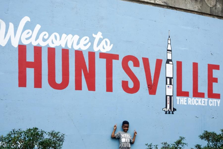 "A child wearing a shirt that says ""Change The World"" poses in front of the Welcome to Huntsville mural."