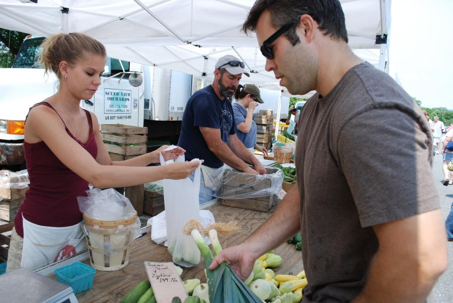 Man purchasing leeks at the Frederick Farmers Market