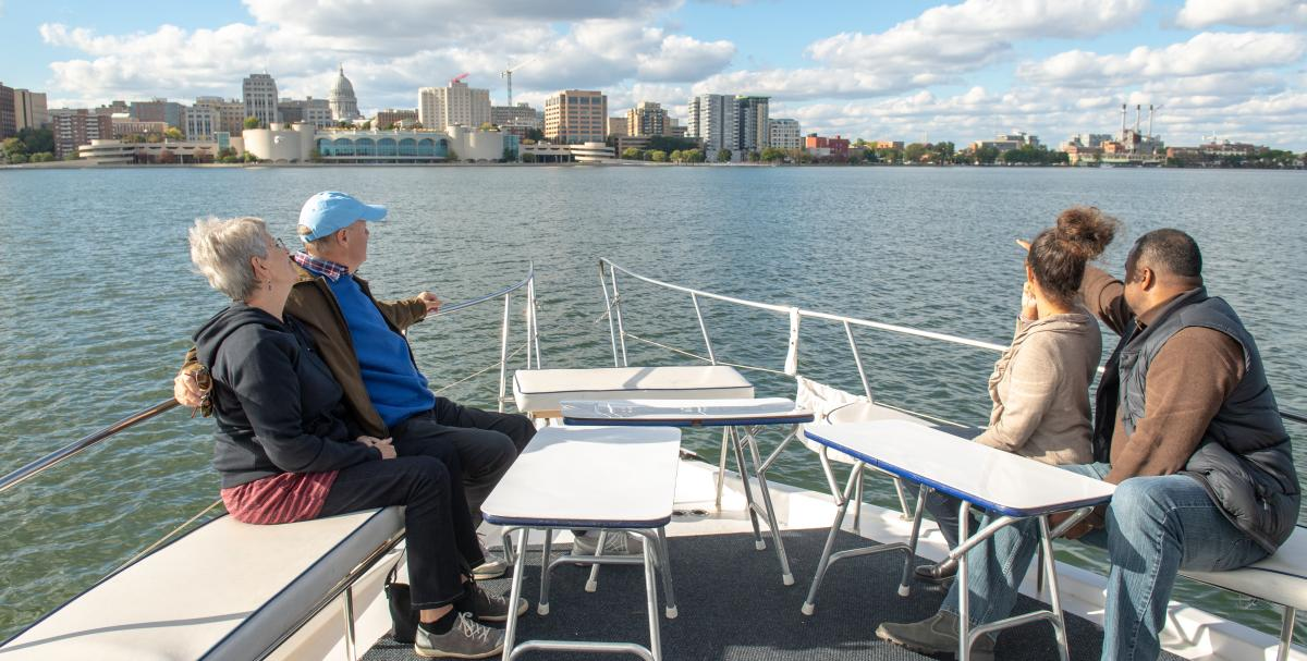 Four participants view the Madison, WI skyline from the bow of a boat