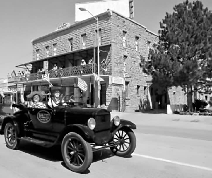 A vintage car drives down the street in front of Hotel Eklund in Clayton, NM