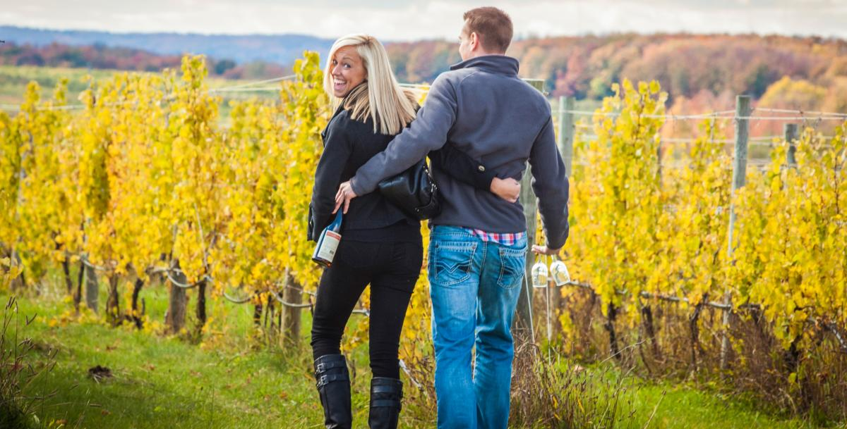 Couple walking with arms around each other with a bottle of wine at the Old Mission Peninsula in the Fall