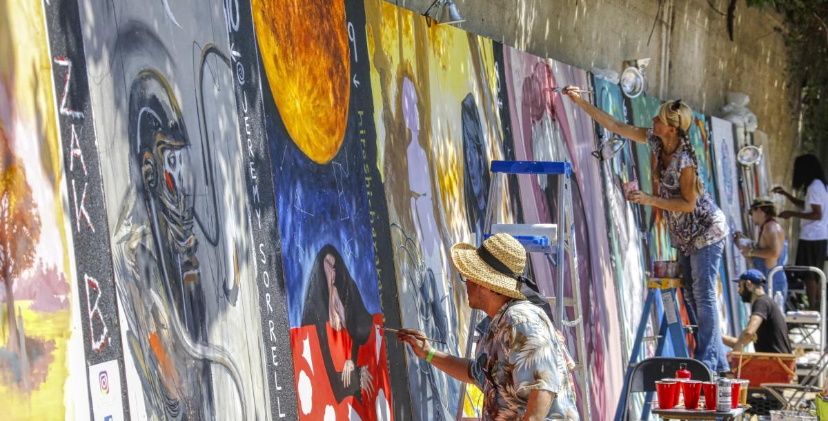 Live mural painters with vibrant artwork at Urban Scrawl in Franklinton
