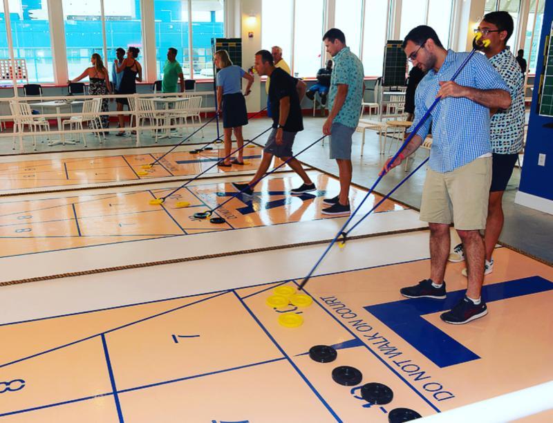 Groups playing indoor shuffleboard at Beachside Social