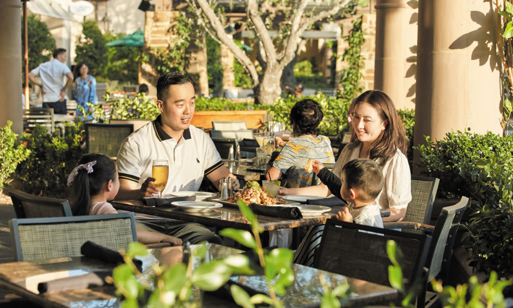 Family Sitting At Restaurant Table Outside
