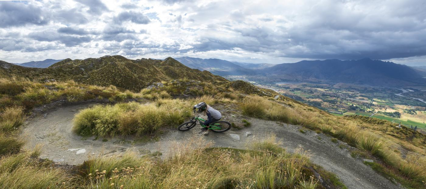 Female mountain biker riding Coronet Peak in summer