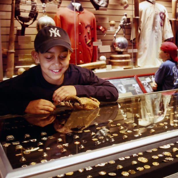 Kid in Yankees hat looking at display at National Baseball Hall of Fame