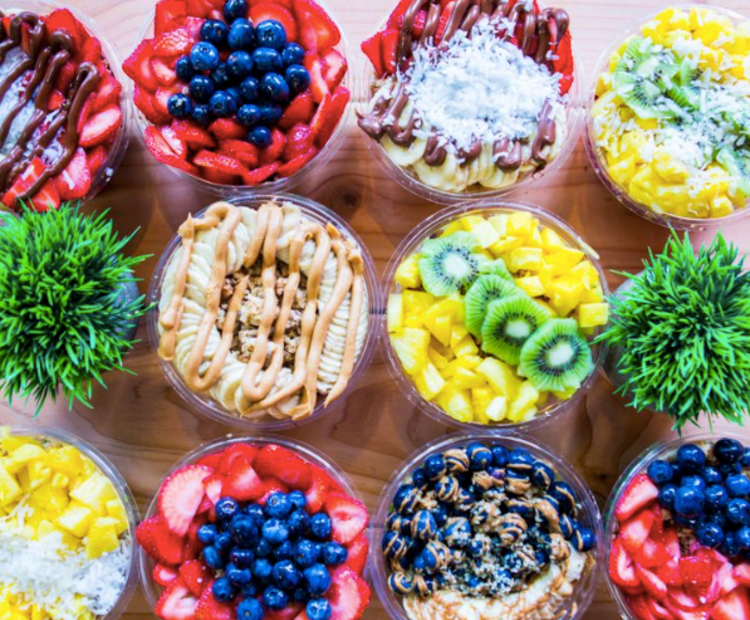 Many bowls filled with different kinds of colorful fruit and smoothies