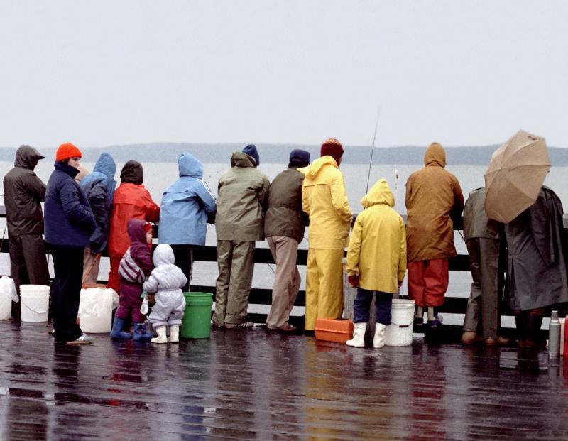 People in rain coats fishing off pier