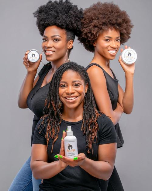 Three women pose with Arcani Coil Care hair product.