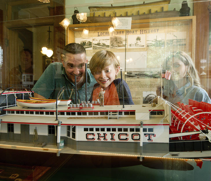 Family looking at a steamboat model at Howard Steamboat