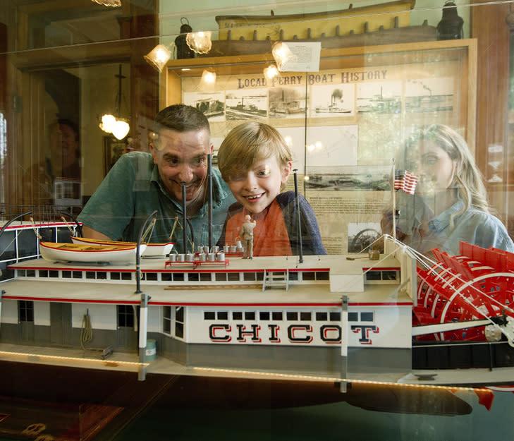 Family looking at a steamboat model at Howard Steamboat