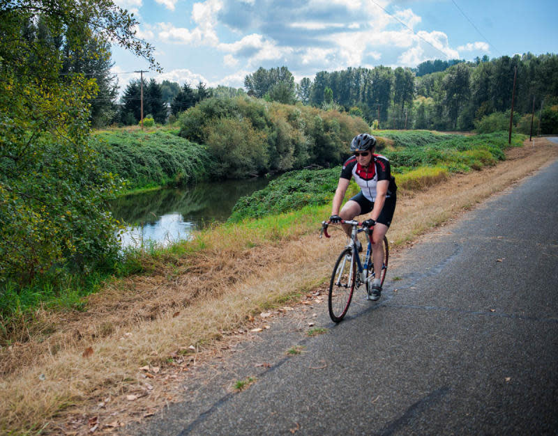 Man Cycling on Seattle Interurban Trail Next to Green River