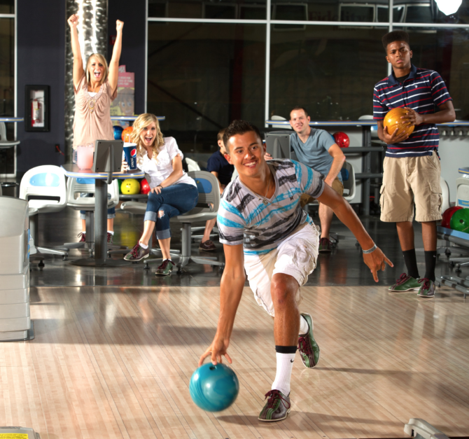 A family bowls together at a bowling alley