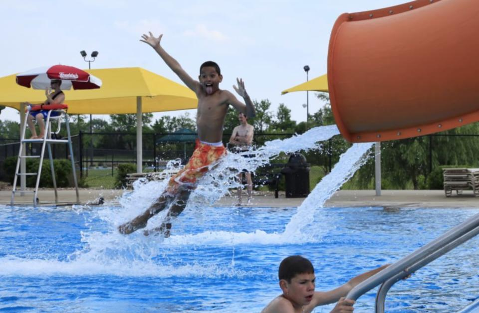 A young boy makes a face at the camera while he shoots out of a water slide at Rock River Rapids