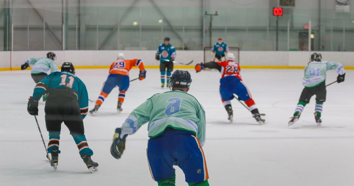 Eight hockey players in different coloured jerseys skate toward a hockey net.