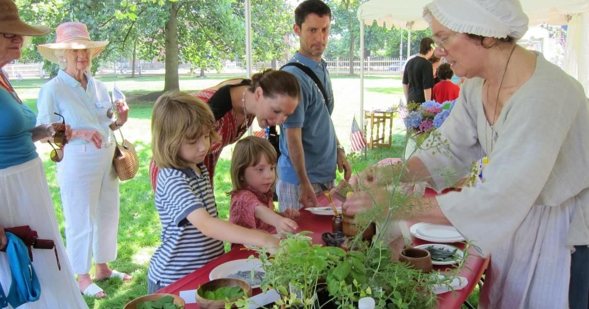 Children and families interact outside at a table with a woman dressed in traditional colonial clothing. Plants and plates are on the table and the children explore the plants.