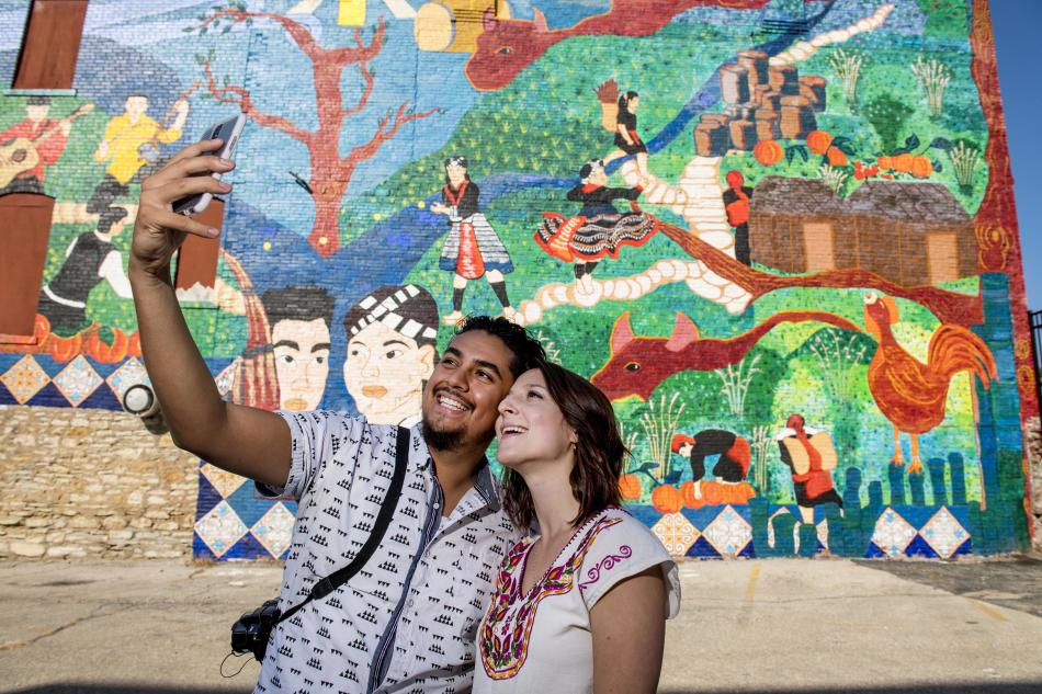Man and woman taking selfie in front of a Hmong mural in downtown Kansas City, KS