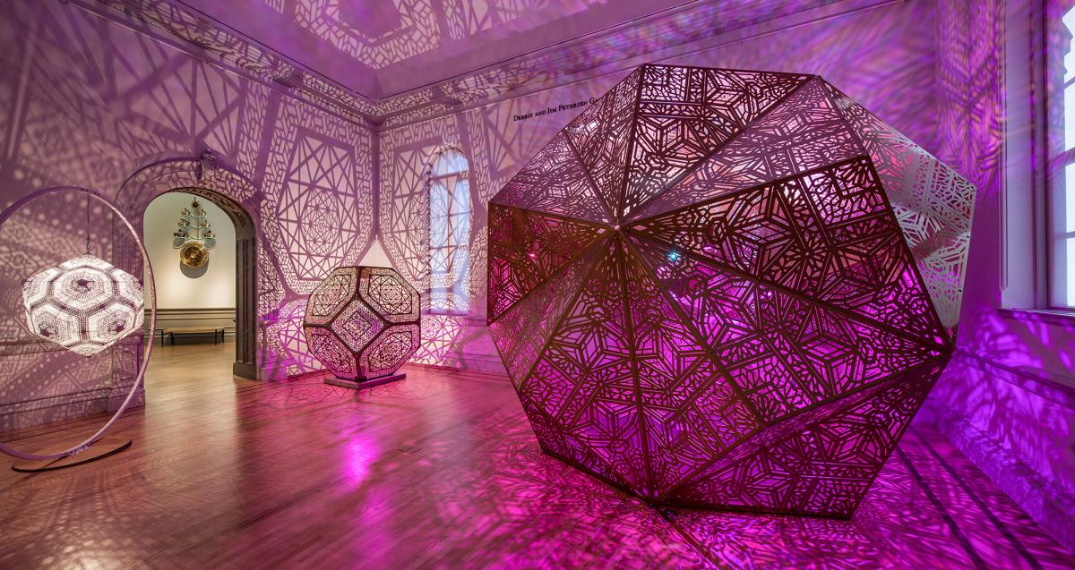 Large paper sculptures from Burning Man illuminated with pink and purple light