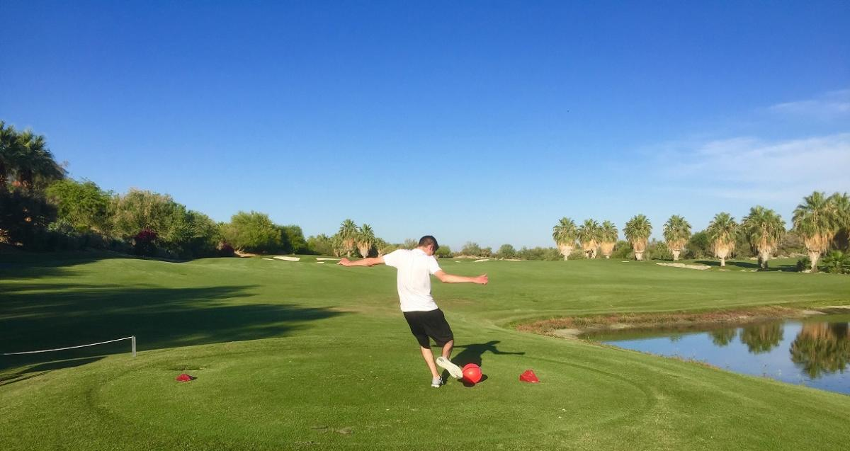 A young person kicks a ball off a tee while playing FootGolf at Desert Willow Golf Resort in Palm Desert.