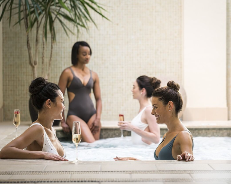 Friends sip drinks while enjoying time in a hot tub at the Four Seasons Resort spa in Irving.