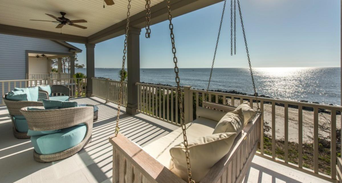 A sunny screened in porch overlooks the Atlantic Ocean at this Jekyll Island vacation rental