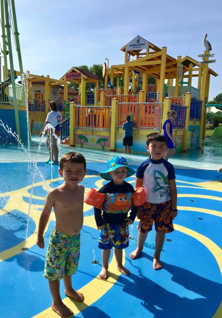 Three boys standing in front of water slides at Sunlite Pool in cincinnati ohio
