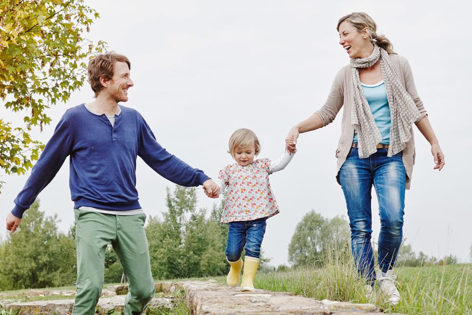 Mom and Dad Holding Girls Hand Stock Photo