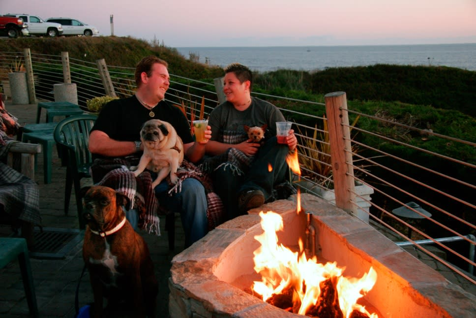 Enjoying a beer with your dogs at Moss Beach Distillery's dog friendly patio
