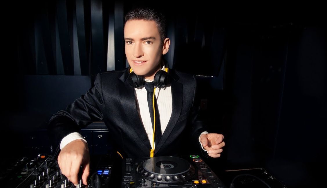 A young man in a suit working on music equipment as a DJ