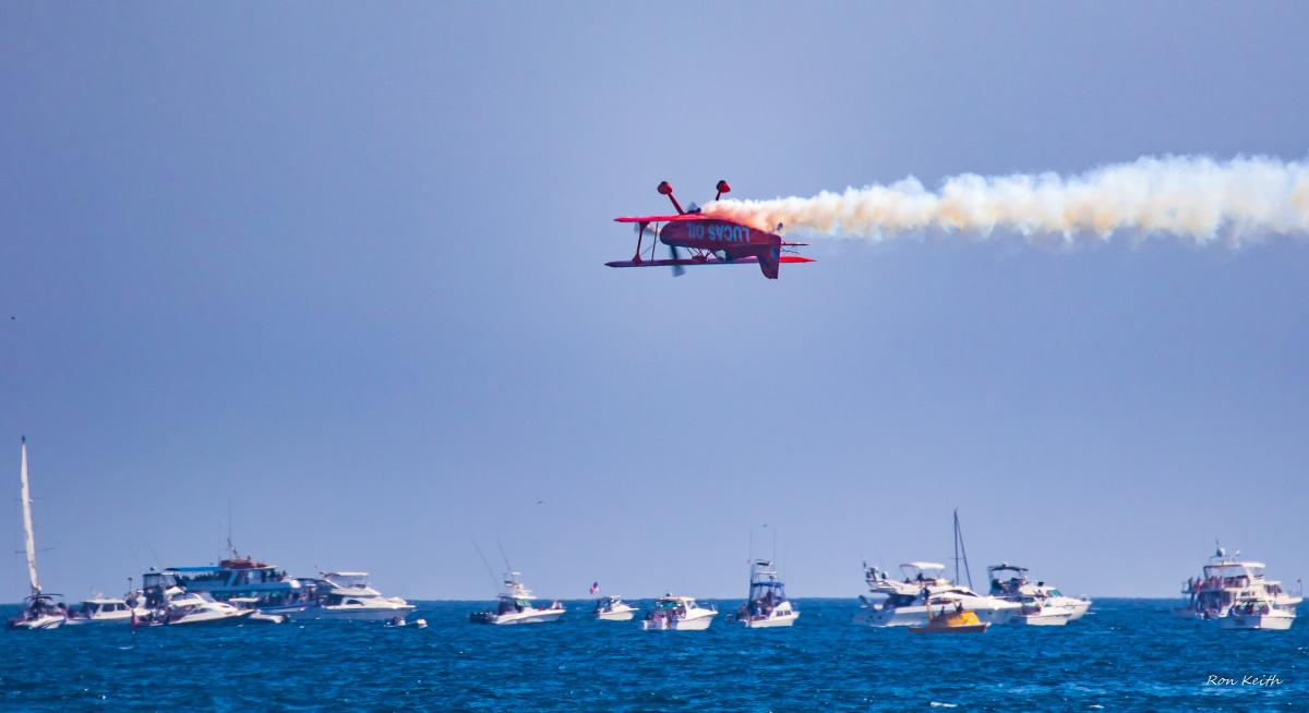 Biplane flying upside down during the Great Pacific Airshow in Huntington Beach