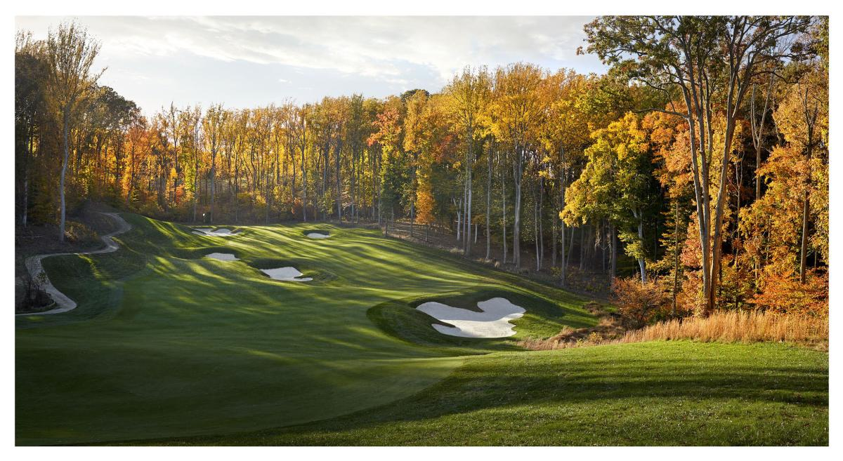 A golf course surrounded by trees with fall foliage