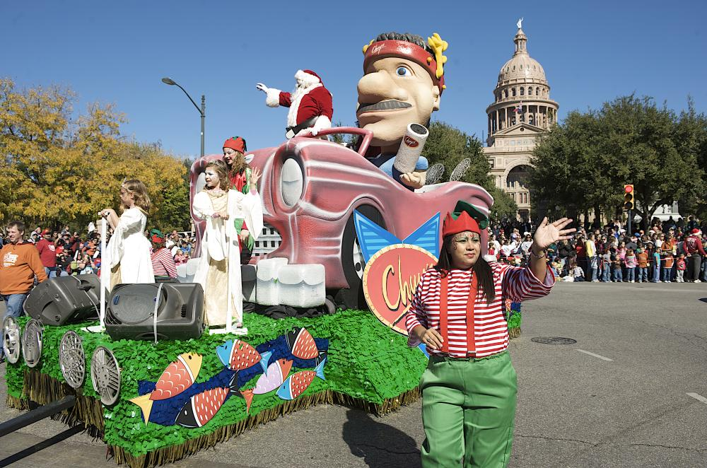 Woman dressed as elf in front of Chuys holiday float with Santa