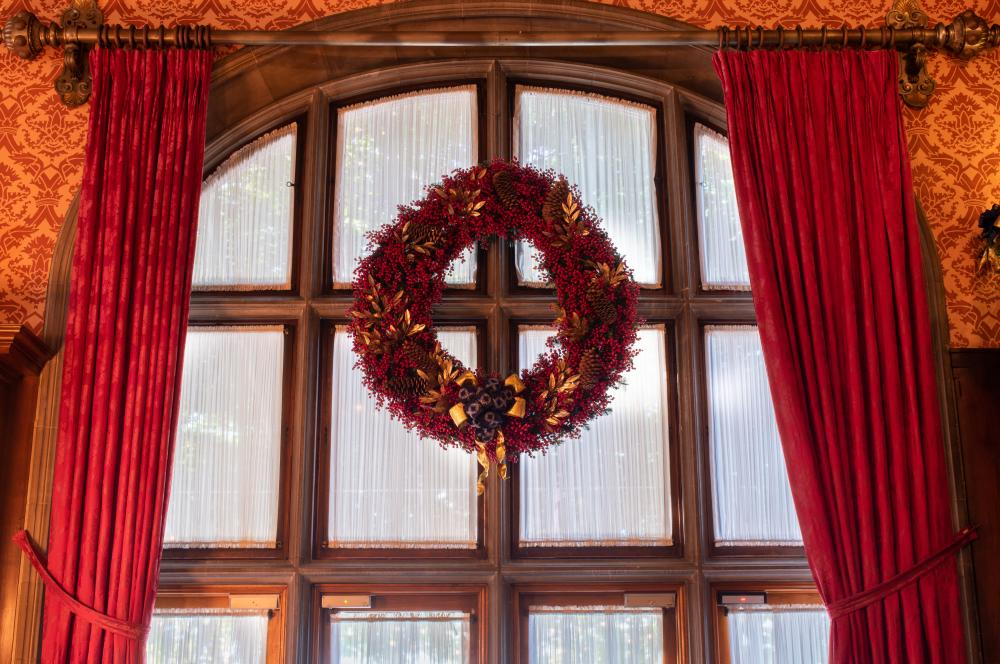 A large crimson wreath adorns a window inside the Library during Christmas at Biltmore