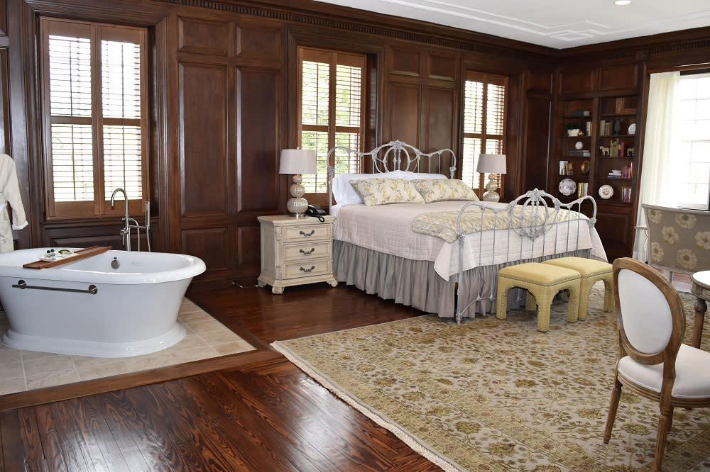 a room at an inn, the room has wood paneling, a bathtub, a side-table, a bed with a white comforter, foot stools and a chair with hardwood floors and a white and gold floral rug.