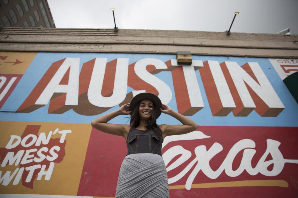 girl posing in front of Austin Texas mural