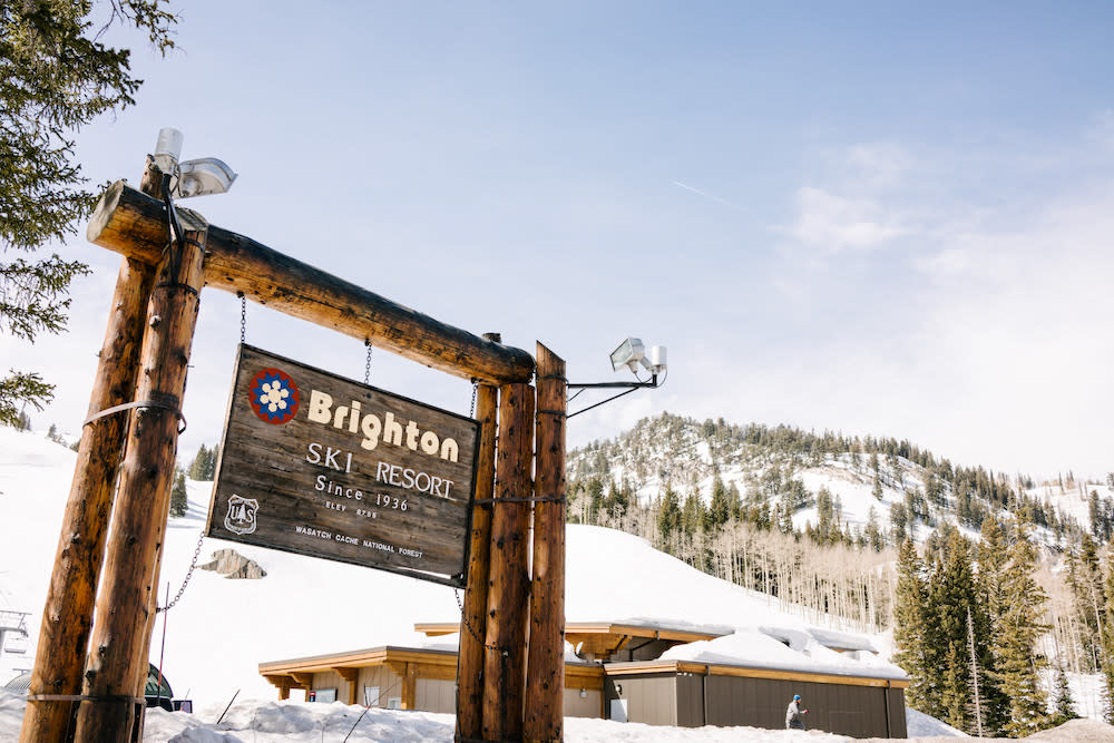 Brighton Ski Resort wooden sign in front of a snowy mountain and snow-covered building