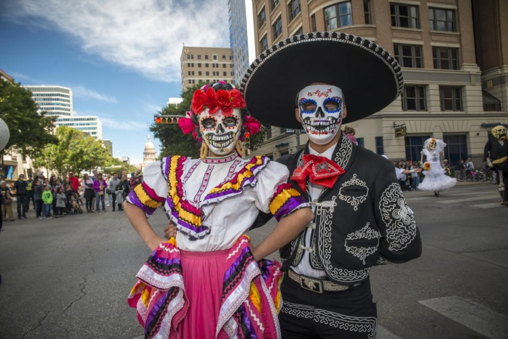 man and woman with dia de los muertos face paint and traditional clothing at Viva la Vida street parade in austin texas