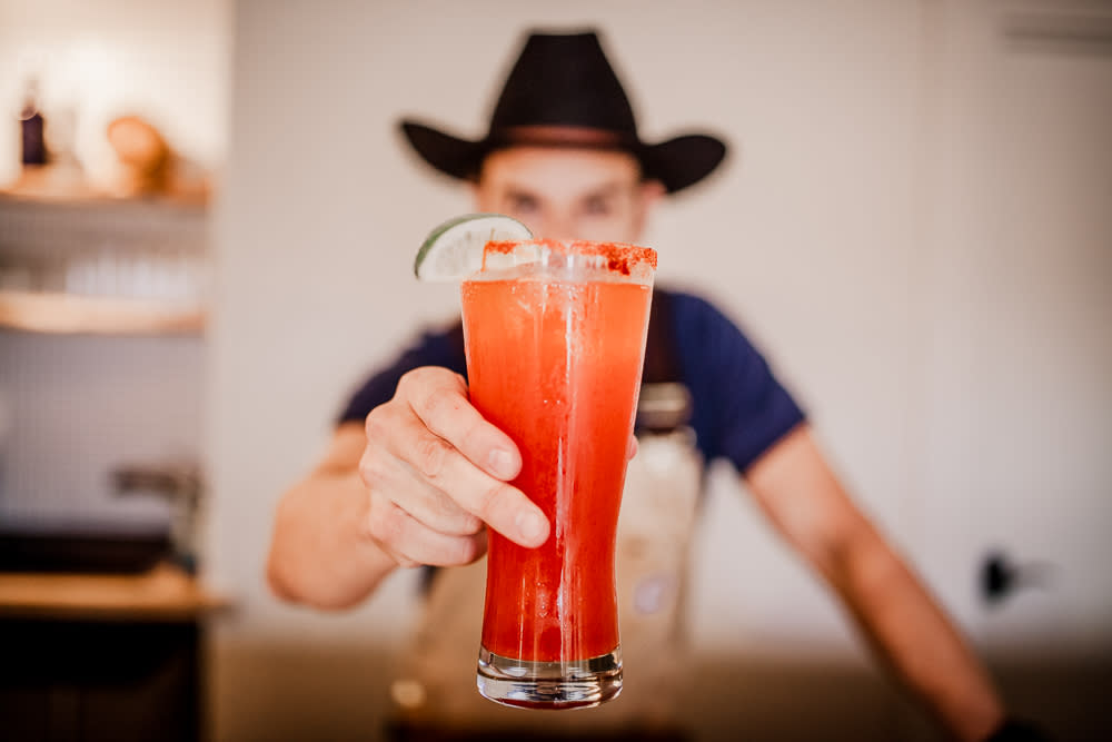 Bartender holding Michelada at Desert Door Distillery near austin texas