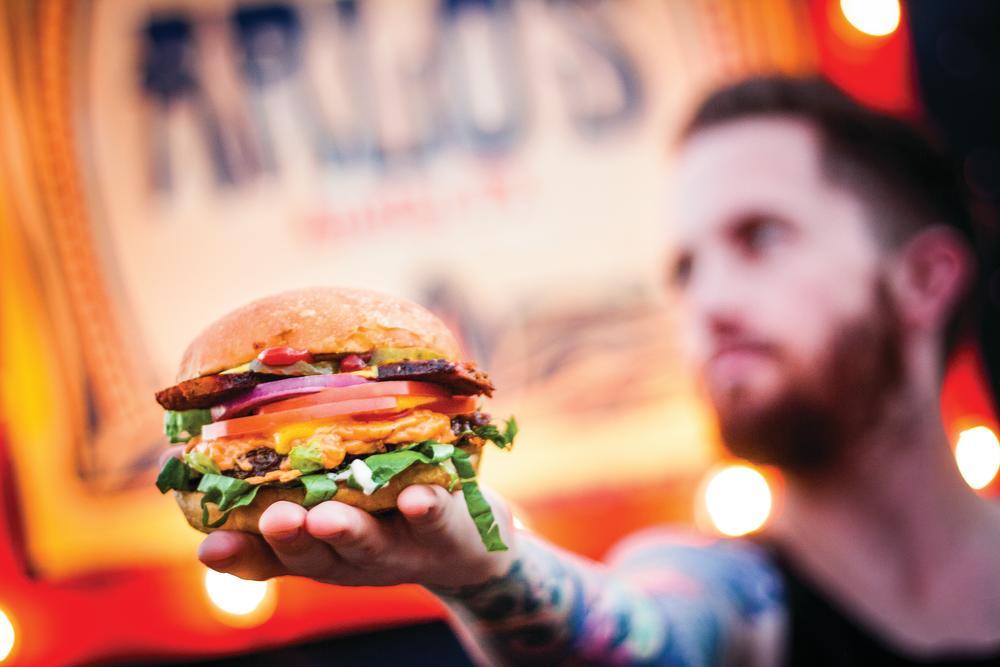 Owner Chris Baker with Vegan Bacn Cheeze Burgers at Arlos Food Truck