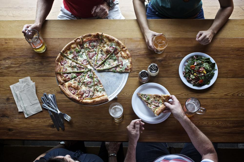 People with pizza and beers at ABGB Austin Beer Garden Brewing Company in Austin Texas